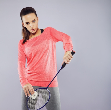 badminton racket: Portrait of attractive young woman with badminton racket ready to serve. Female badminton player playing against grey