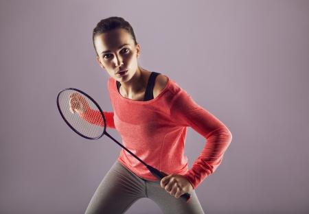 을 들고 아름 다운 여자 배드민턴 라켓은 회색에 재생. 여성 스포츠 인 배드민턴 선수는 카메라를 찾고.