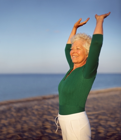 stay beautiful: Portrait of beautiful mature woman practicing yoga on beach with copyspace. Old caucasian woman exercising outdoors to stay fit. Health and fitness concept. Stock Photo