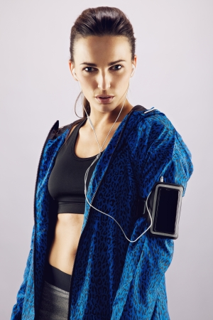 armband: Portrait of pretty young woman in sportswear listening to music with mobile phone on armband. Beautiful young female athlete standing against grey background