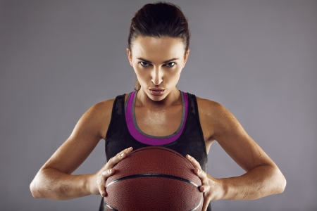 Portrait of female basketball player in studio. Young woman in sportswear holding basketball looking at camera against grey background photo