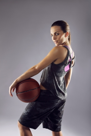 Portrait of beautiful young woman basketball player looking over shoulder at camera against grey background. Female basketball player posing for camera. photo