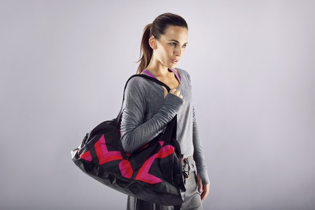 Portrait of fit young woman carrying gym bag looking away at copyspace over grey background. Beautiful caucasian female ready for gym exercise. Stock Photo