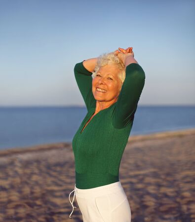 Happy elder woman looking relaxed on the beach with her hands on her head. Active senior female on the beach relaxing photo
