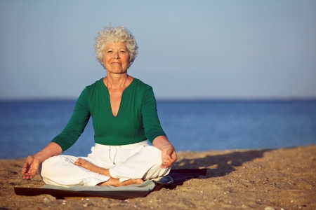 Portrait of senior woman meditating on sandy beach. Smiling mature woman exercising on seashore with copyspace. Meditation, yoga and relaxation concept photo