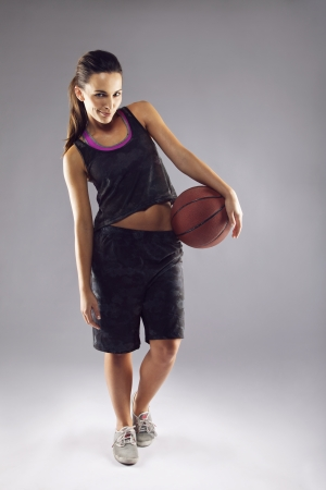 Full length portrait of pretty young female basketball player in uniform holding a basketball posing over grey background photo
