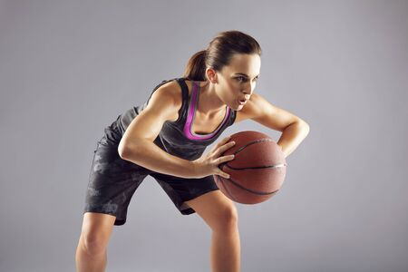 females: Young female basketball player in uniform passing a basketball. Woman in sportswear playing basketball and looking away on grey background Stock Photo