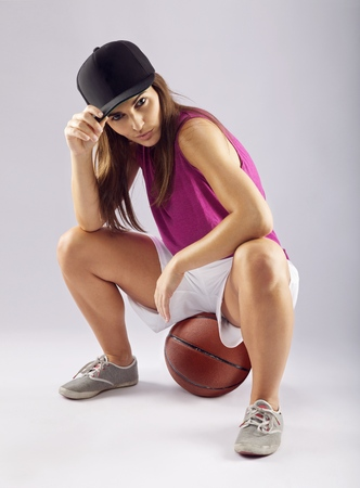 Beautiful and sporty woman sitting on basketball over grey background. Caucasian female basketball player looking at camera. photo