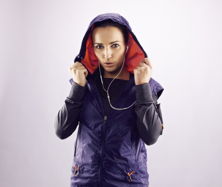 Portrait of beautiful young woman in sportswear looking at camera. Confident female runner in hoodie against grey background photo