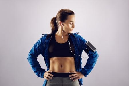 armband: Giovane donna che indossa abbigliamento sportivo guardando telefono cellulare sul bracciale. Atleta donna che ascolta la musica con il cellulare su sfondo grigio