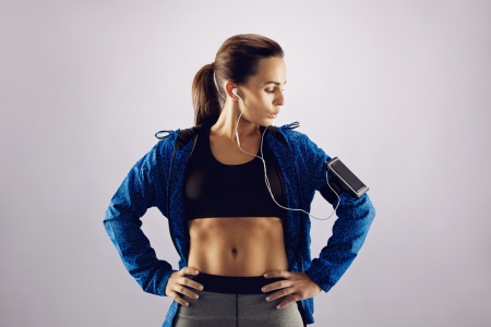 sports wear: Young caucasian woman wearing sports wear looking at mobile phone on armband. Female athlete listening music with cell phone on grey background