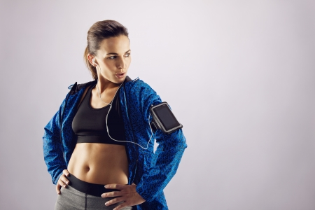 Portrait of beautiful fitness woman wearing sportswear looking away at copyspace while standing on grey background. Young caucasian female in sports gear posing. photo