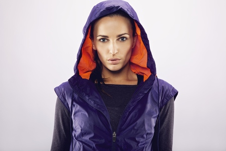 Portrait of beautiful young caucasian woman in a hooded jacket on grey background. Fitness woman in sportswear looking at camera photo