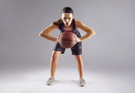 Full length portrait of female basketball player passing the ball over grey background. Beautiful female in sportswear holding playing basketball. photo