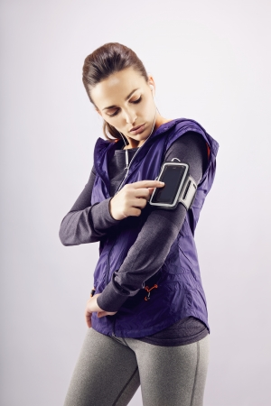 Young caucasian woman wearing earphones listening to music on mp3 player. Female runner listening music on grey background photo