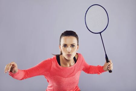 Portrait of young sports woman playing badminton against grey background. Fit athlete playing badminton. Caucasian woman in sportswear holding racket playing badminton photo