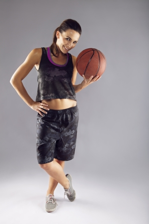 Full length portrait of young woman in sports uniform holding a basketball over grey background. Happy female basketball player standing confidently looking at camera photo