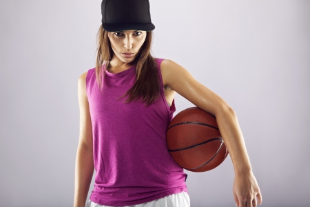 Female basketball player holding ball against grey background. Young woman holding basketball looking at camera confidently photo