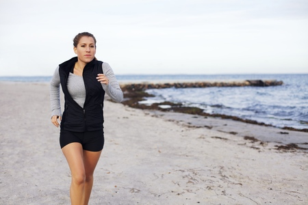 Healthy young female jogging on seashore. Beautiful caucasian woman athlete running and exercising on the beach with copyspace - Outdoors photo