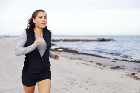 Fit and healthy woman jogging on beach. Beautiful young female model running outdoors. Caucasian female training on the beach with copyspcae photo