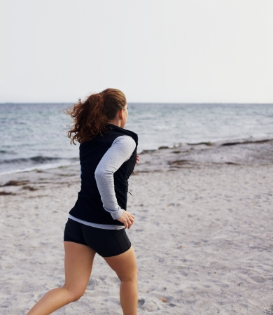 Healthy young woman running on seashore. Young caucasian female model jogging on beach outdoors. Female runner training on sandy beach. photo