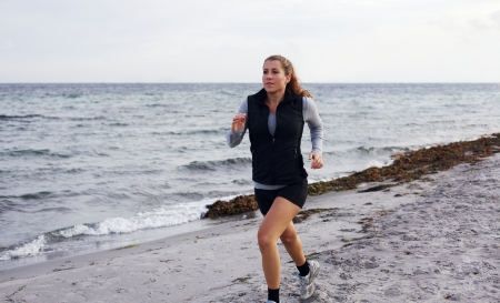 Portrait of healthy young woman jogging at the beach. Beautiful female model running on shoreline outdoors. photo