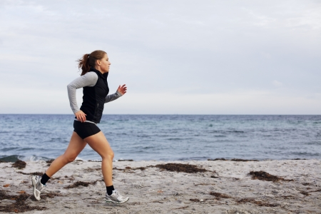 Fit and healthy young woman running along shoreline. Caucasian female athlete exercising running on beach. Beautiful young woman runner running on beach. photo