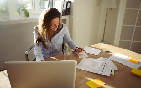 Pretty young female writing notes smiling. Beautiful caucasian female with laptop computer working from home office.