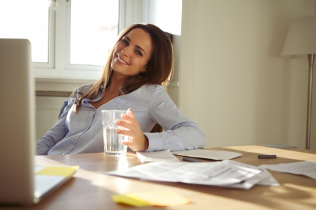working from home: Pretty businesswoman sitting at her desk with a glass of water looking at camera smiling. Confident young caucasian woman working from home office. Stock Photo
