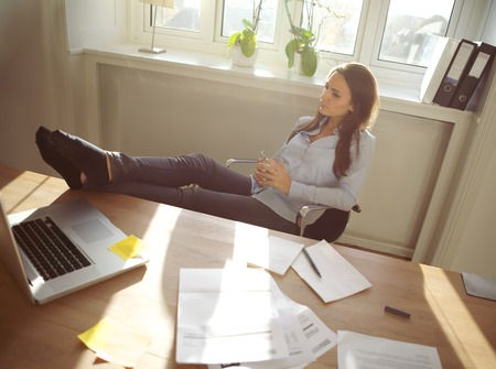 taking a break: Young beautiful businesswoman at table resting with her legs on desk. Thoughtful caucasian female relaxing at her desk. Young woman taking a break from work at home office.