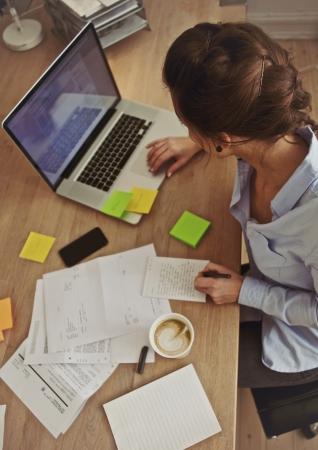 경치: 직장에서하는 동안 노트북을 사용하는 젊은 갈색 머리의 오버 헤드보기. 그녀의 책상에서 작업하는 사업가.