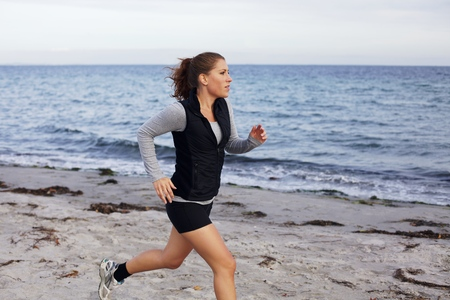 Female runner running on seashore. Woman jogging outside in sports clothing. Beautiful fit young female fitness model. Woman runner training on beach. photo