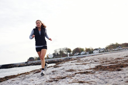 Young woman jogging along beach wearing sports clothing. Healthy female running on sea shore. Female runner exercising outdoors photo
