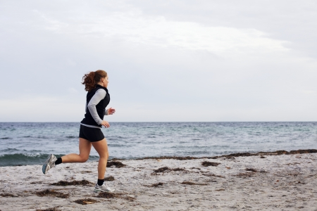 Young female athlete jogging during outdoor workout on beach. Fit and beautiful young woman running. Female runner going outdoor workout on seashore. photo