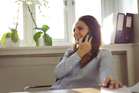 at her desk: Pretty young woman talking on mobile phone while sitting at her desk. Beautiful businesswoman working from home office.