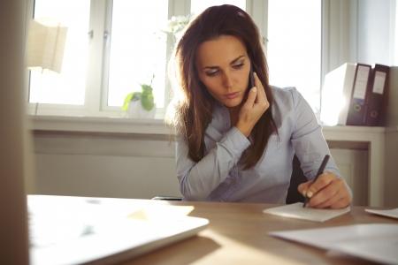 携帯電話で話していると、彼女の机に座ってノートを書く若い女性。ホーム オフィスで働くかなり白人女性。