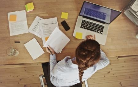 문서 및 노트북 그녀의 사무실 책상에서 일하고 젊은 갈색 머리의 높은 각도 볼 수 있습니다. 서류 작업을하는 사업가.