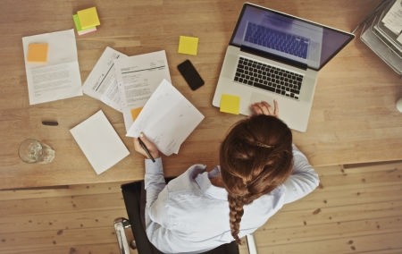 dolgozó: Magas, szög, kilátás egy fiatal barna dolgozik az irodájában íróasztal dokumentumok és laptop. Üzletasszony, dolgozik a papírmunkát.