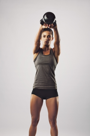 Pretty young woman swinging kettle bell weight with both hands. Crossfit female working out on grey background photo