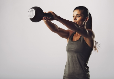 bell: Image of young attractive female doing kettle bell exercise on grey background. Fitness woman working out. Crossfit exercise.