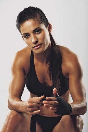 toughness: Beautiful young female boxer wearing black strap on wrist. Muscular built woman getting ready for boxing exercise on grey background