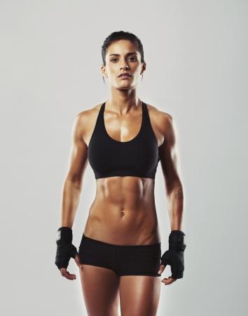 회색 배경에 서있는 거친 젊은 여자. 근육 여성의 카메라를 찾고 있습니다. 체육관 운동을위한 준비 장갑을 착용하는 여성 보디.
