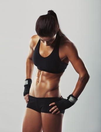 hip: Muscular young woman athlete standing looking down with her hands on hips on grey background. Woman bodybuilder relaxing after exercise.