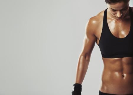 Close-up beeld van Midden-Oosterse vrouw in sportkleding ontspannen na training op een grijze achtergrond. Spier vrouwelijk lichaam met zweet. Afbeelding met copyspace voor tekst Stockfoto