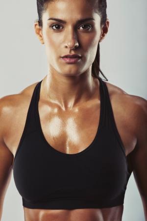회색 배경에 카메라를 찾고 스포츠 브래지어에서 젊은 여자의 이미지를 닫습니다. 운동 후 근육 이완 빌드 여성. 피트니스와 보디 빌딩 훈련.