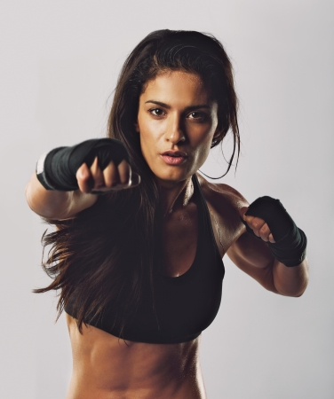Portrait of young sport girl training boxing against grey background. Hispanic female practicing boxing looking at camera. Female boxer throwing a punch in front. photo
