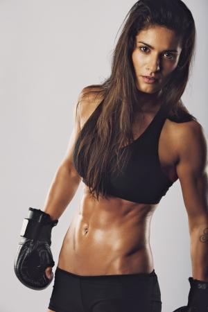 Vrouw kickboksen vechter met een intense blik. Gespierde vrouw met bokshandschoenen kijken naar de camera tegen een grijze achtergrond Stockfoto