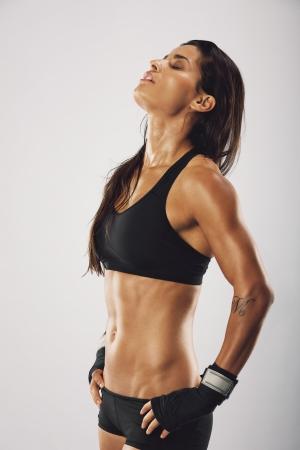 Vrouwelijke bokser gevoel uitgeput na de training. Vrouw bokser op zoek moe na het boksen praktijk op een grijze achtergrond.