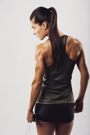 culturista: La imagen vista trasera de culturista femenina sosteniendo cuerda de saltar la mirada. Fitness mujer joven con cuerpo musculoso posando sobre fondo gris
