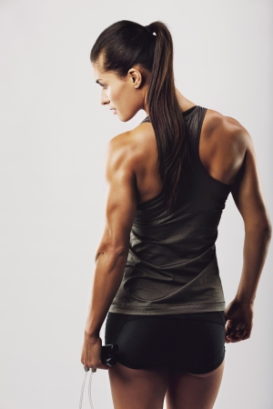 Rear view image of female bodybuilder holding skipping rope looking away. Young fitness woman with muscular body posing on grey background photo